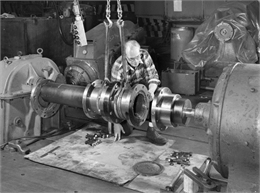 "A male employee, Al Arndt, attends to a slide coupling. Falk caption reads, ""Photos of a special slide coupling. Size 50GL32S... See Engineering File for exact specifications. Assembly drawing 424364."""