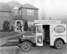 Parked in the foreground along a curb is an International Model M-2 milk truck owned by Pevely Selected Milk Co.