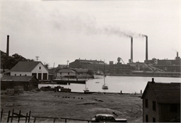 A view across Kenosha harbor at the large Simmons Company factory building.
