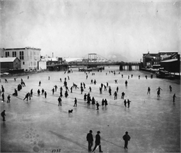 Elevated view of a large group of people skating on the frozen Manitowoc River between the 8th and 10th Street bridges.
