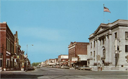 Color postcard of downtown Antigo, at the intersection of 5th Avenue and Superior Street looking north.