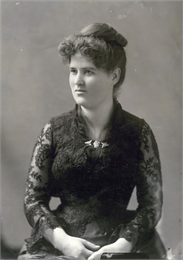 Formal studio portrait of Belle Case La Follette wearing a black lace dress.