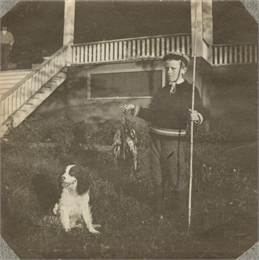 A young Aldo Leopold poses proudly with his bamboo fishing pole, stringer of fish and a dog.
