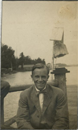 A young Aldo Leopold poses smiling wearing a jacket and bow tie while seated on a pier.