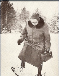An image of Dr. Kate Pelham Newcomb wading through the snow, wearing snow shoes.