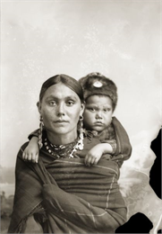 A woman in Ho-Chunk regalia wrapped in a blanket, with a child on her back. The child wears a fur hat, and she has on long earrings, and a necklace. They are posed sitting in front of a painted backdrop.