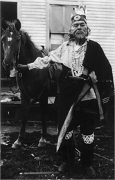 Candid portrait of Potawatomi Chief Simon Onanguisse Kahquados holding the bridle of a horse.