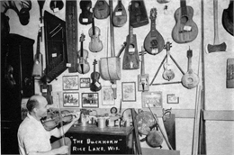 Otto Rindlisbacher, folk singer and maker of stringed instruments, sitting in his shop holding a Hardanger fiddle.