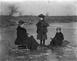 Florentina, Jennie, and Edgar Krueger prepare for ice skating on the quarry pond. Florentina and Edgar sit on sleds on the ice, as they attach blades to their shoes. Jennie stands between them.