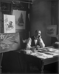 International Harvester advertising artist sitting at his desk in a studio office with a wistful look on his face. Graphics from Deering brand advertisements are propped up behind him. The photo was likely taken at the company's McCormick Works.