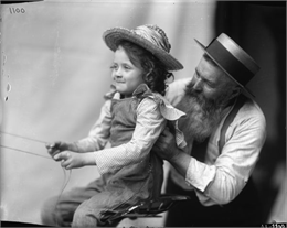 A young girl sits in the seat of a farm implement and holds onto reins as an older bearded man assists. The image was likely used as a model for advertising art.