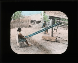 Outdoor view of one woman using a loom and another woman preparing fibers for the loom to create siding for housing.