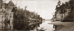Panoramic view from shoreline of the Wisconsin River in the Wisconsin Dells. A sandy beach area is on the right, and rock formations are on both sides of the river.