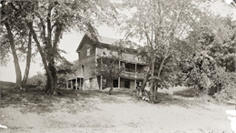 Exterior view of Dell House with two women posed in front.