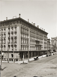 Elevated view of Newhall House. A number of horse-drawn vehicles are parked along the curb.