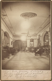 Interior view of lobby area of Newhall House hotel with several people sitting in chairs.