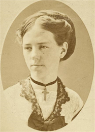 Studio portrait of young Clara Bewick Colby wearing a cross necklace.