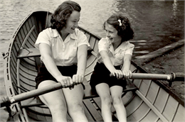 A camp counselor and young camper look at each other and smile in a rowboat in the water.