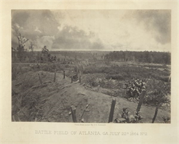 An empty battlefield with posts sticking out from an earthworks in the foreground.