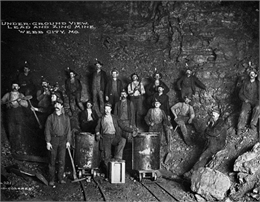 A photograph of men standing along the sides of a lead mine in Webb City, MO.