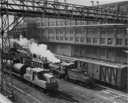 Black and white photo showing an elevated view of Milwaukee railroad yards showing several trains on the tracks next to a large industrial building.