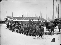 Group portrait black and white photo of men, women. children and dogs posed standing, sitting and holding logging tools in a snow-covered logging camp in front of log buildings.