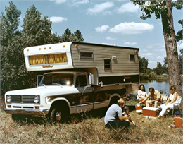Color advertisement of a family camping near a lake with an International 1310 pickup truck and a Monitor camper.