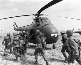 Black and white image of infantry troops boarding helicopters for Korea via the 6th Transportation Helicopter Company.