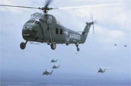 Aerial view of flock of U.S. Marine helicopters in the sky over Vietnam. One of the dark green and yellow helicopters is in the foreground. Four others trail close behind.