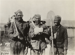 Three African American soldiers with a company of engineers somewhere in France. They are holding a shovel, pick, and sledgehammer.