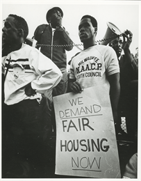 "A man holds a sign that reads, ""We Demand Fair Housing Now,"" while others behind him use a bullhorn."