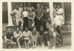 Group of young adults standing on porch of house
