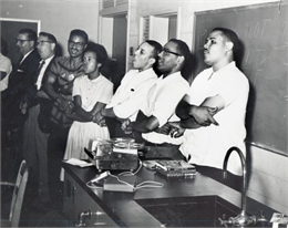 A group of people sing and hold hands while standing at the front of a classroom