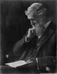 Photographic portrait of John Muir seated and reading a book.