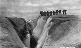 Photograph of a tourist group on Muir Glacier near a ravine.
