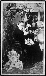 Portrait of Mathilde Franziska Anneke seated, surrounded by flowers and plants.