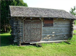 Photograph of a state historical marker for the Radisson-Grosseilliers Fort, mounted to the side of a log cabin.