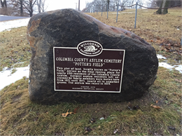 Photograph of historic marker for Columbia County Asylum Cemetery Potter's Field mounted on boulder