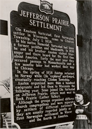 Photograph of a young girl posing with the historic marker for the Jefferson Prairie Settlement