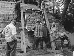 Photograph of construction workers installing historic marker for Solomon Juneau House