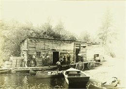 View across water towards the Gang standing in front of G. Swenson's Store in Kettle Falls, which is partially on the water.