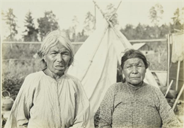 Two elderly women posing in front of a tipi (teepee) at a settlement near Moose River.