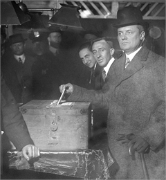 New York Governor Charles Seymour Whitman votes using a similar simple wooden ballot box, 1915-1918