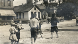 "A group of boys ""following their leader in search of adventure"" in the street. The boys are barefoot and are wearing hats. In the background are a storefront, houses, and wooden wagons."