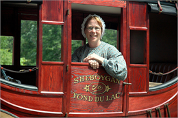 A woman in historical garb sits inside a stagecoach.