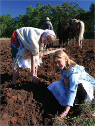 Two girls help work in the fields.