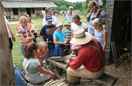 A group of school children surround a shingle maker.