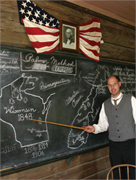 A teacher point to a drawing of Wisconsin on the blackboard.