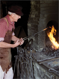 A blacksmith works with fire.