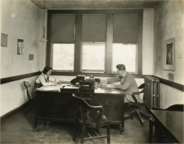 Martin P. Winther seated at desk.